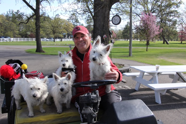 Bill Israelson with his dog in a golf cart.