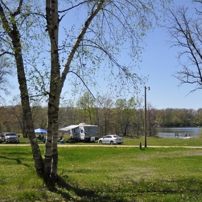 A small camper parked near the lake at Dower Lake Campground.