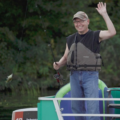 Man in a boat catches a fish at Dower Lake in Staples, MN.