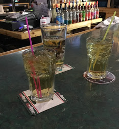 Three drinks sit on the bar.