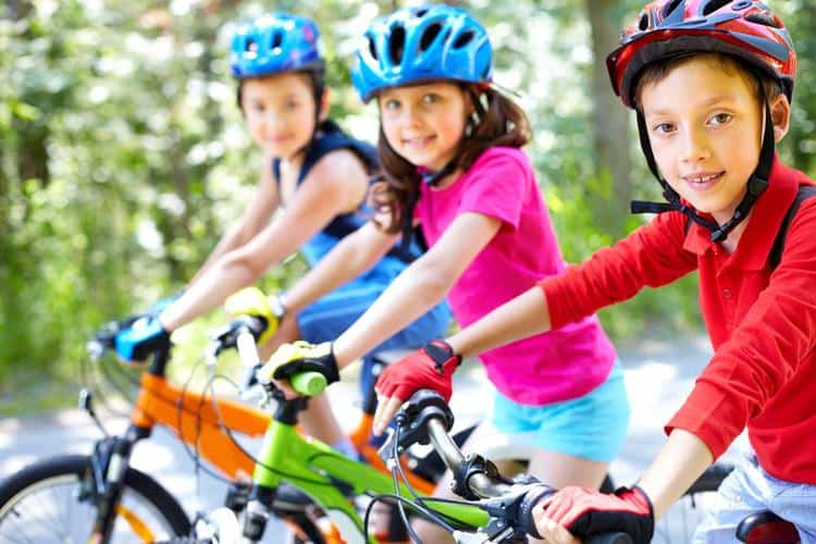 3 kids on bikes with helmets