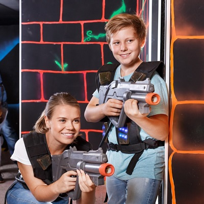 A mom and son play laser tag.