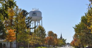 The Staples watertower rises above the trees lining the city street in fall.