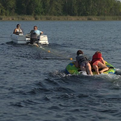 A boat pulls two children on a tube at Dower Lake in Staples, MN.